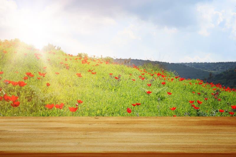 在领域红色鸦片前面的木土气桌 产品显示和野餐概念 库存图片