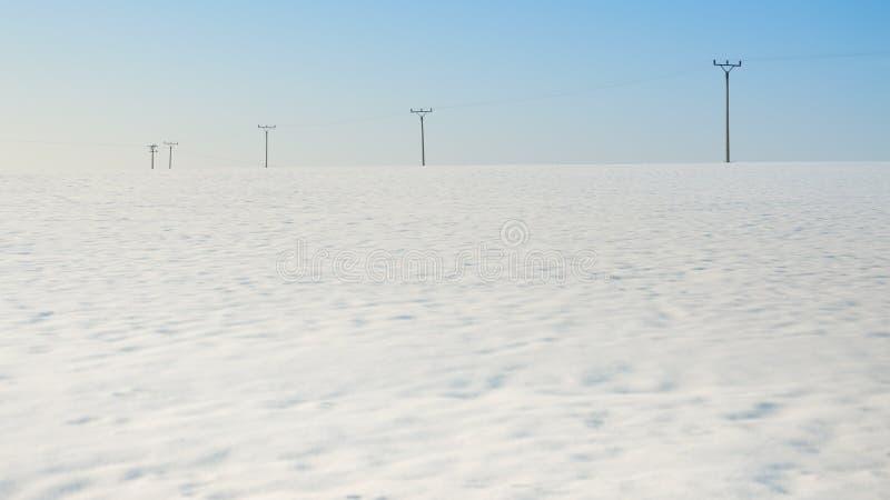 在领域,冬天季节的电杆 免版税库存照片