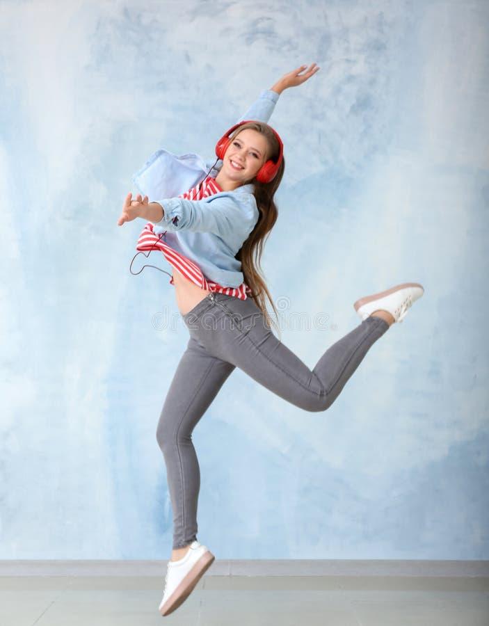 在颜色墙壁附近的美好的年轻女人跳舞 库存图片