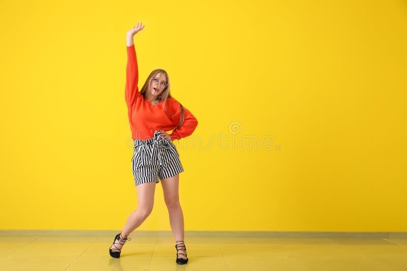 在颜色墙壁附近的美好的年轻女人跳舞 库存照片