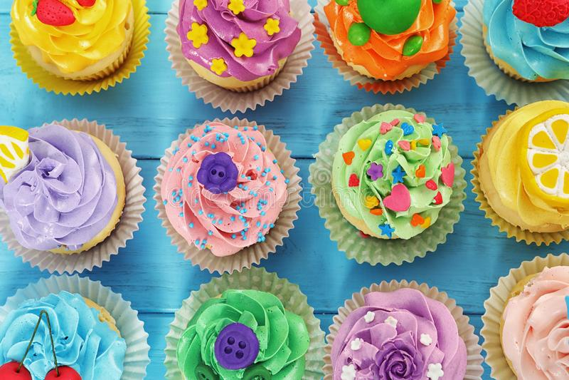 在颜色木背景的美丽的杯形蛋糕, 免版税库存图片