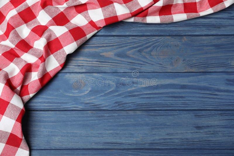 在颜色木背景,顶视图的方格的野餐毯子 免版税库存图片