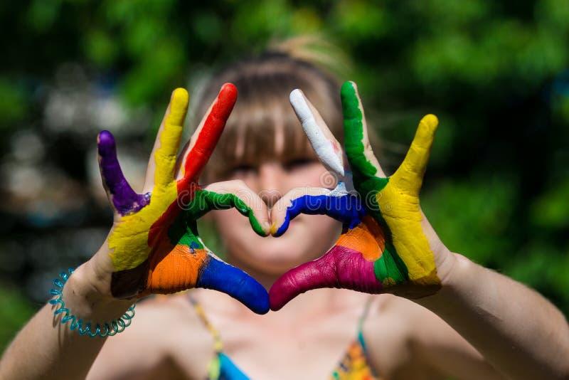 在颜色油漆的孩子手做心脏形状,在手上的焦点 库存照片