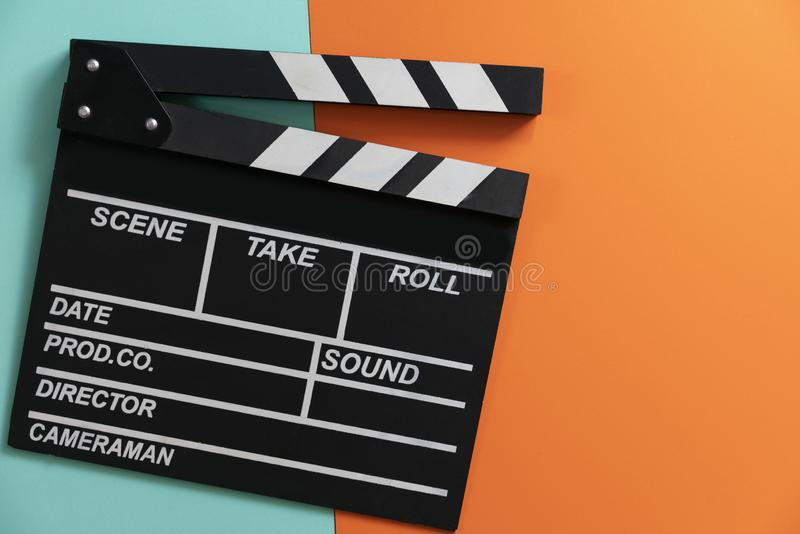 在颜色背景的电影拍板;影片、戏院和录影摄影概念 免版税库存照片