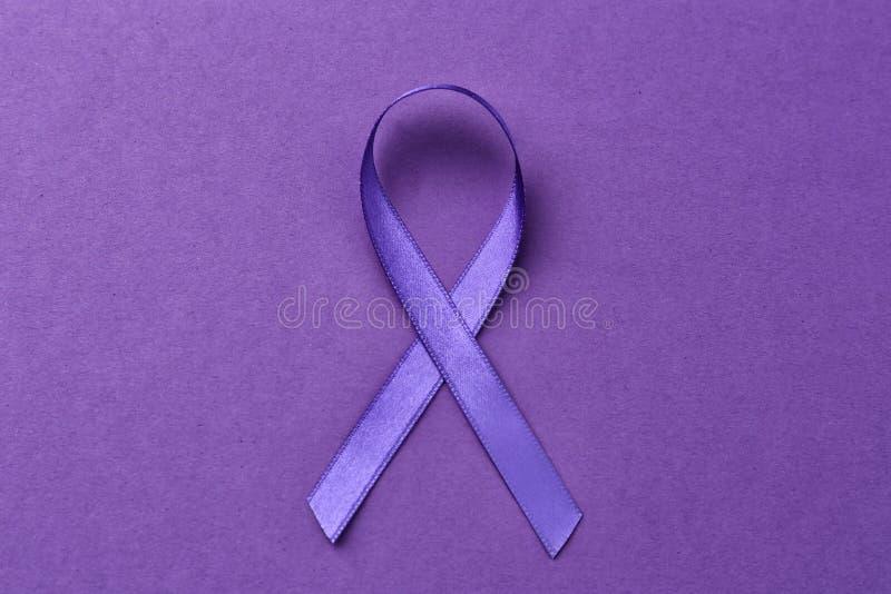 在颜色背景的紫罗兰色丝带 家庭暴力、老年痴呆症和胰腺癌症 库存照片