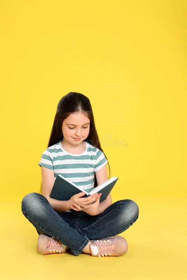 在颜色背景的逗人喜爱的女孩看书 库存照片