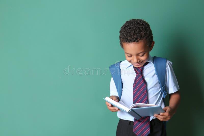 在颜色背景的逗人喜爱的非裔美国人的男小学生看书 库存图片