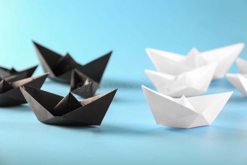 在颜色背景的Origami小船 交锋概念 库存照片