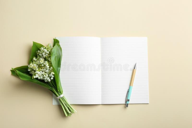 在颜色背景,平的位置的笔记本、笔和铃兰花束 图库摄影