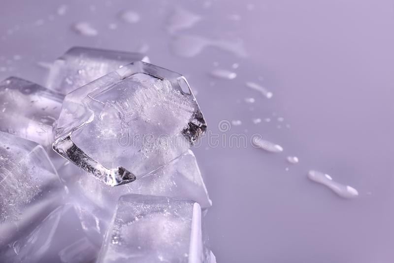 在颜色背景,特写镜头的透明冰块 免版税库存照片