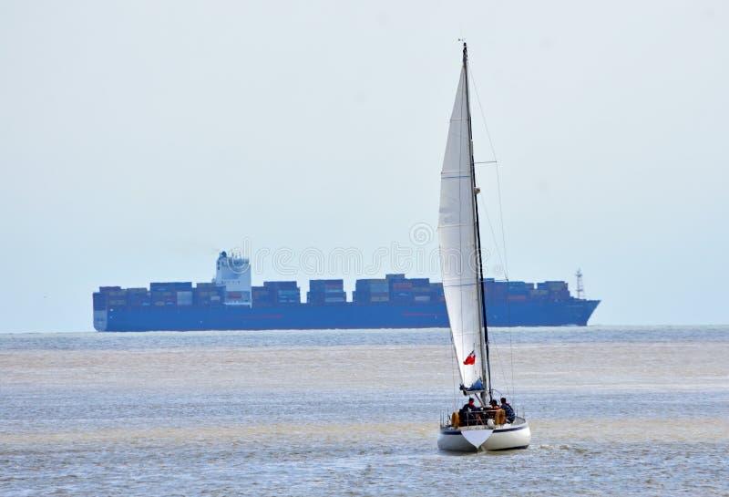 在风帆下的游艇有大集装箱船的在背景中 免版税库存图片