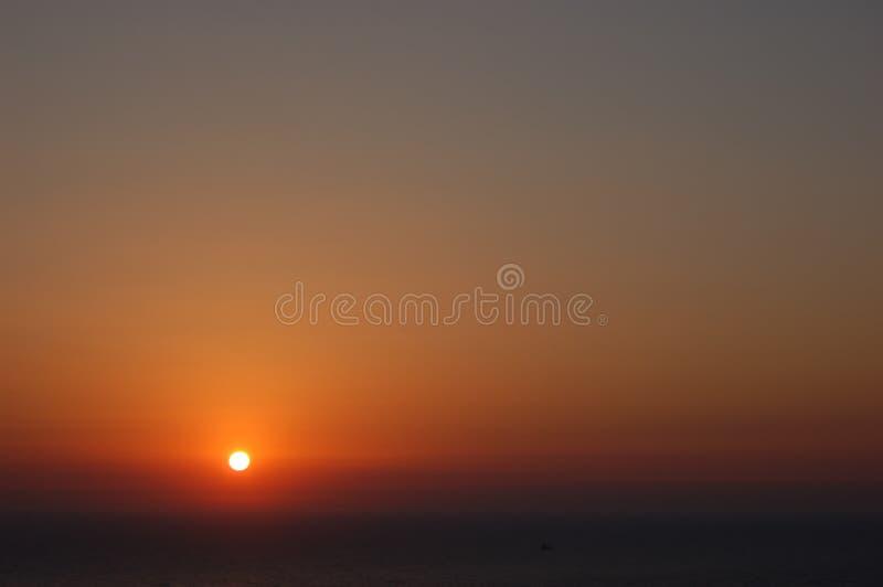 在风平浪静上的橙色日落 免版税图库摄影