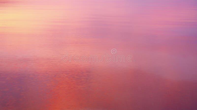 在风平浪静水反映的强烈的日出颜色 库存图片