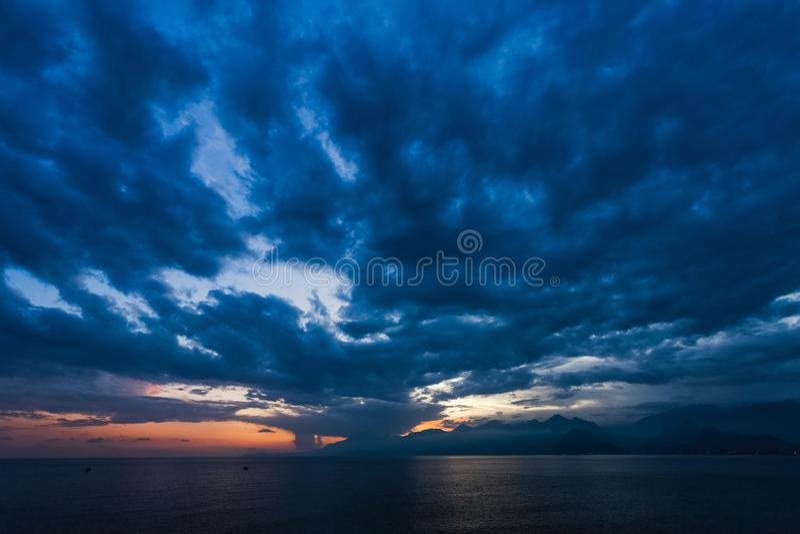 在风平浪静水和山的自然日落或日出时间 免版税库存照片