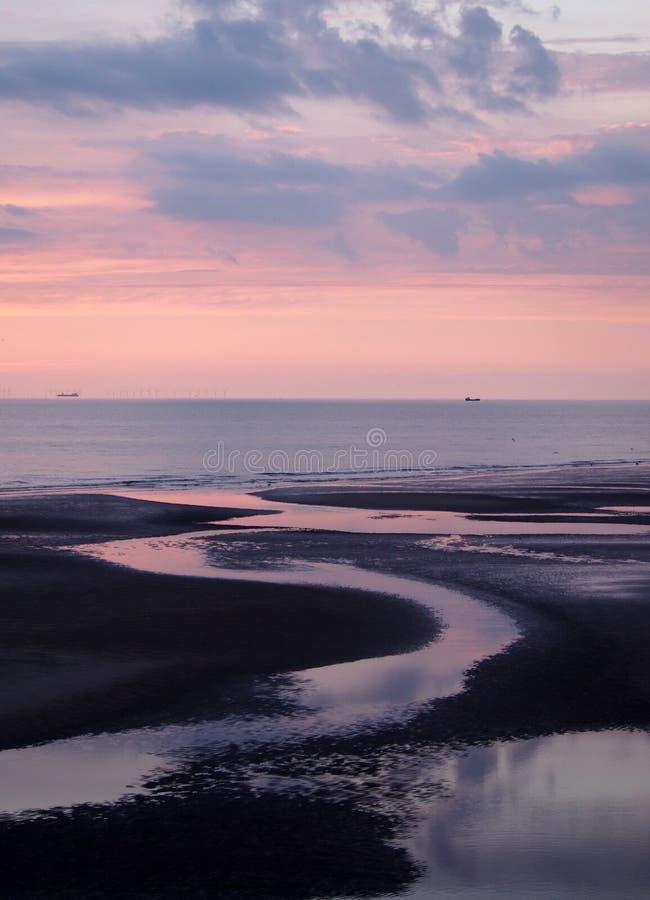 在风平浪静的美好的紫色微明用在反射五颜六色的日落云彩的海滩的水 库存照片