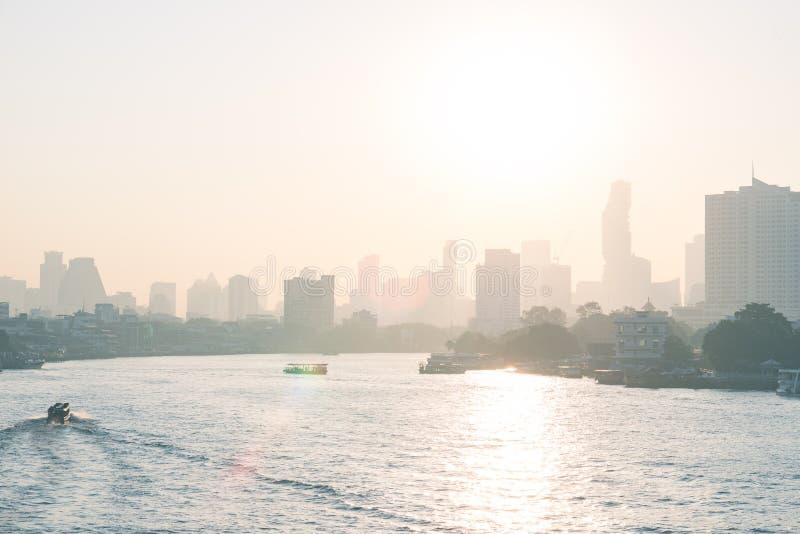 在风景地平线的曼谷日出,首都泰国,背后照明太阳破裂了巡航在昭披耶河的小船 免版税图库摄影