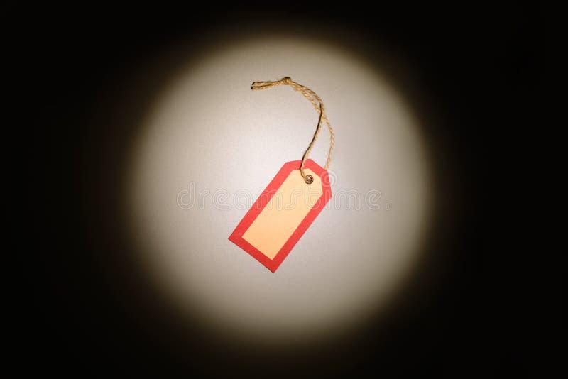 在风景点光光芒的红色购物标签在黑暗的背景的 免版税库存图片