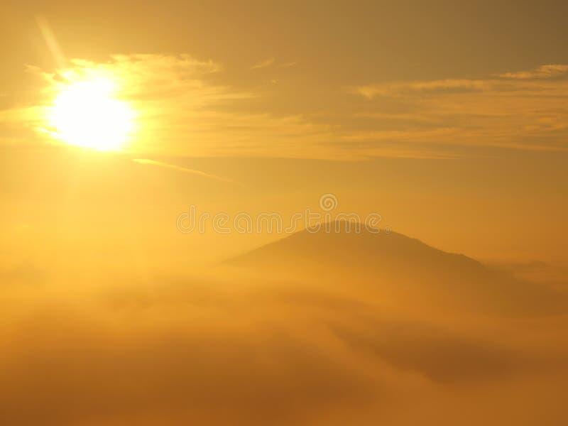 在风景的壮观的重的薄雾 秋天老保守日出在乡下 从雾增加的小山,雾被上色对桔子 免版税库存图片