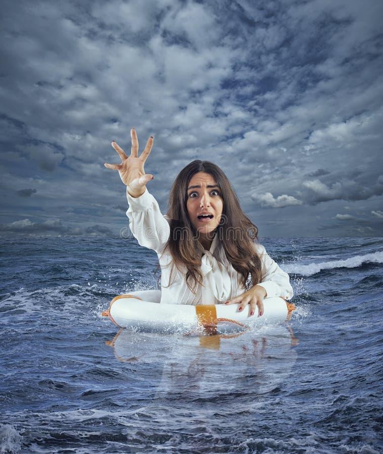在风暴期间,女实业家在有救生带的海洋要求帮助 免版税库存照片