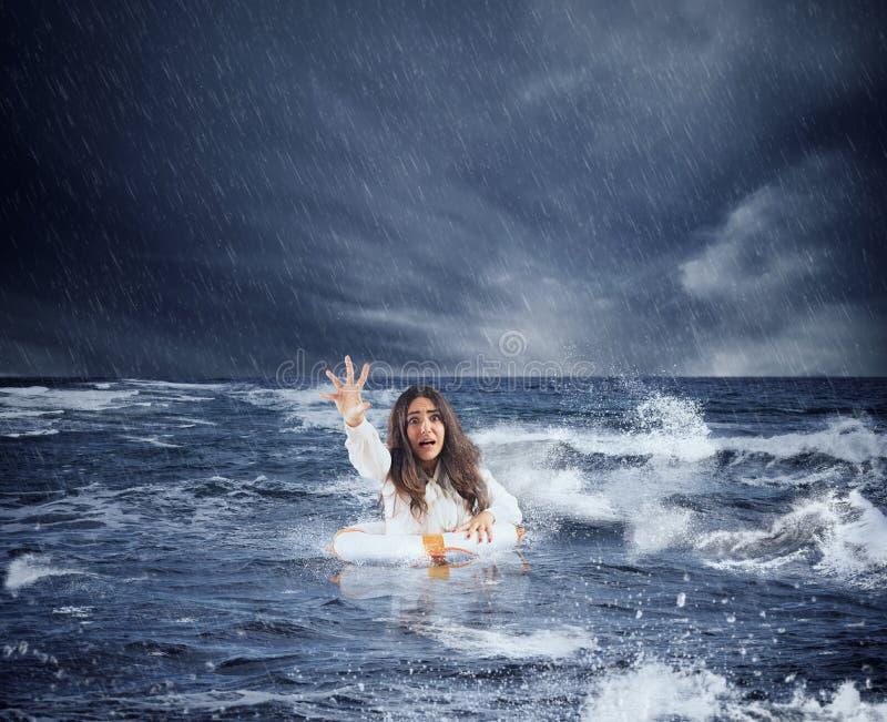 在风暴期间,女实业家在有救生带的海洋要求帮助 免版税图库摄影