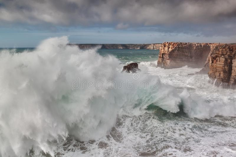 在风暴期间,巨型波浪打破反对岩石, 免版税库存图片