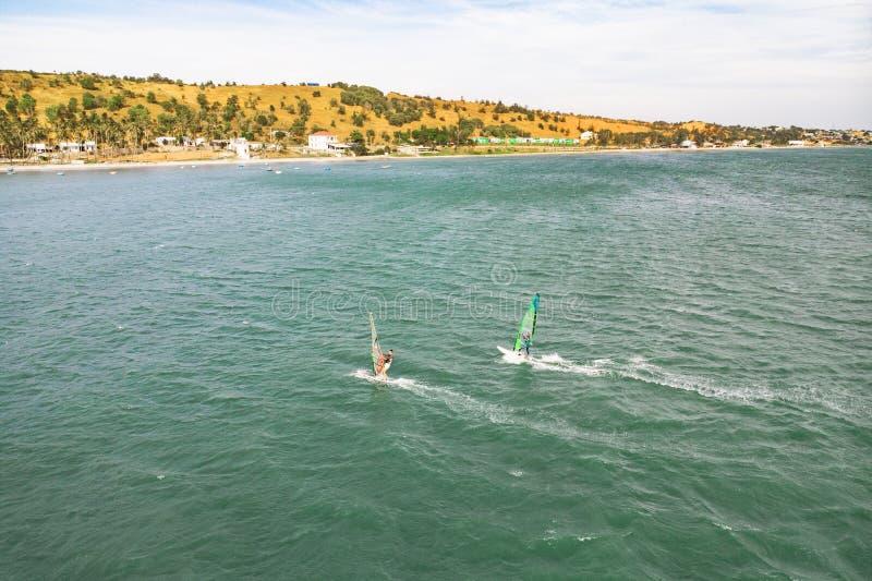 在风海浪的极端人运动员游泳在反对蓝色海和天际的海波浪 极端水上运动 ??  免版税图库摄影