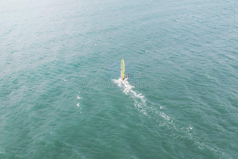 在风海浪的极端人运动员游泳在反对蓝色海和天际的海波浪 极端水上运动 ??  库存照片