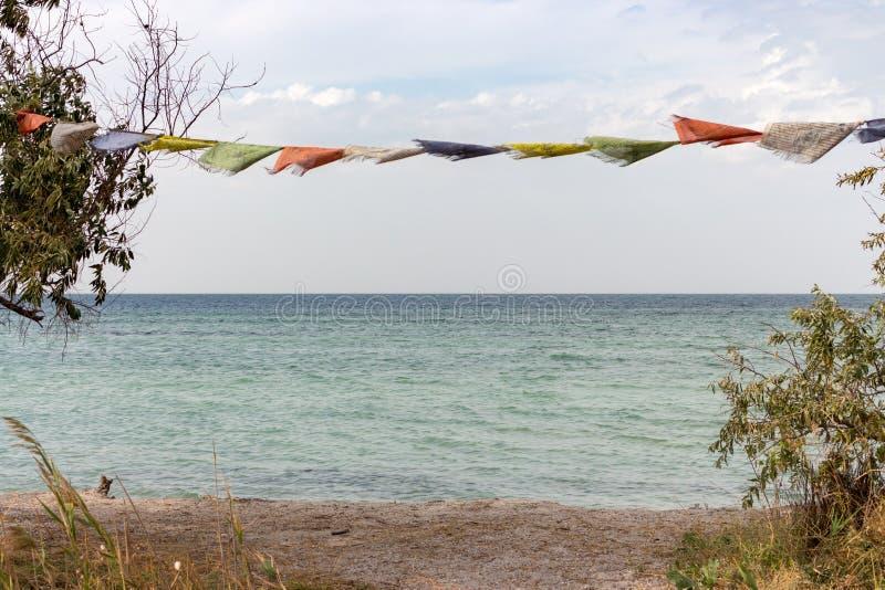 在风的五颜六色的旗子在夏天海阵营 夏天海岸装饰 海边风景 热带旅行概念 免版税库存图片