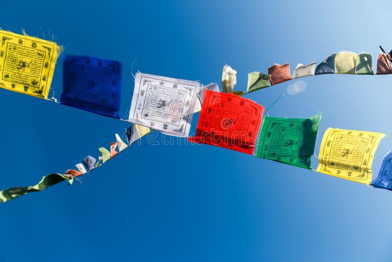 在风的祷告旗子反对一明亮的天空蔚蓝 免版税库存图片