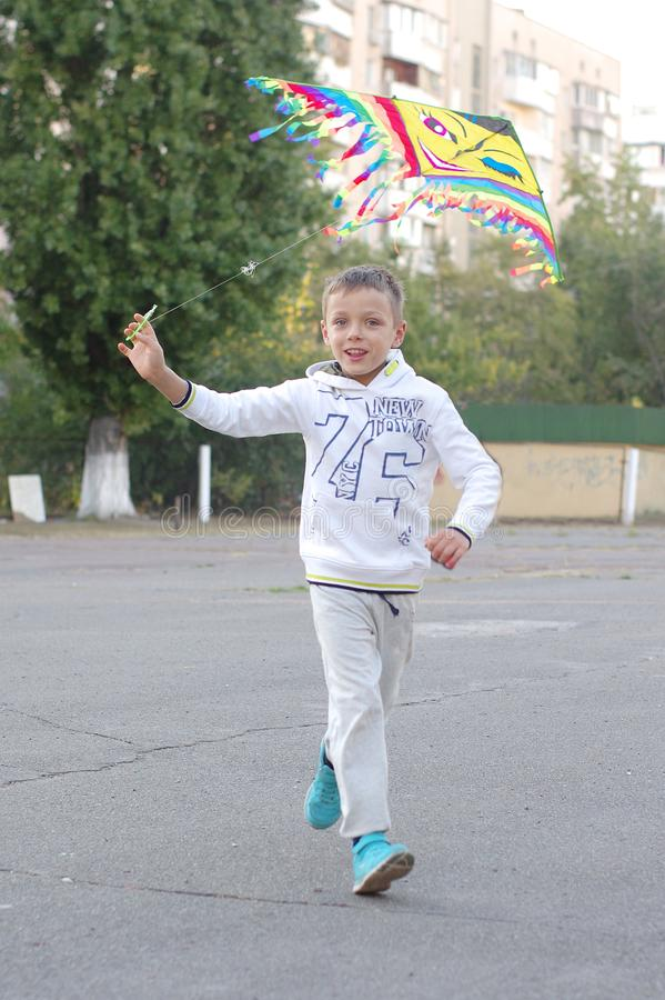 在风筝的滑稽和愉快的儿童游戏 他们在白色运动衫和裤子穿戴 跑在日落 库存照片