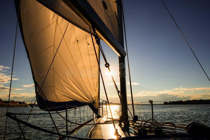 在风船甲板的日落,当在公海或河时的巡航的航行 有充分的风帆的游艇在有风结束时 库存照片