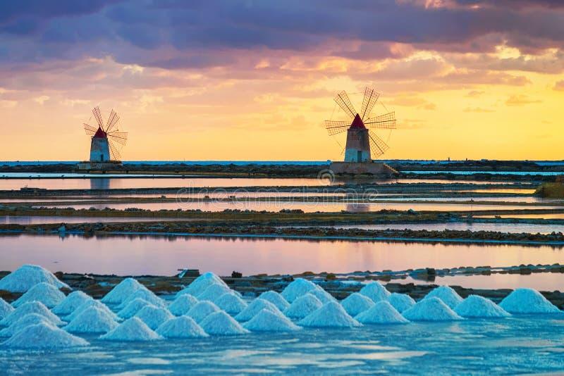 在风车的日落在盐evoporation池塘在马尔萨拉西西里岛 免版税库存照片