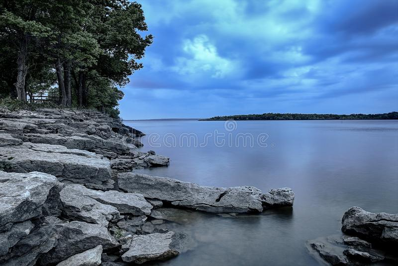 在风雨如磐的日落的湖 图库摄影