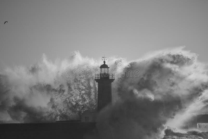 在风雨如磐的波浪飞溅中间的灯塔 库存照片