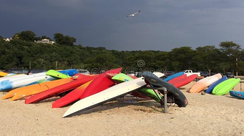 在风雨如磐的海滩的五颜六色的皮船 库存图片