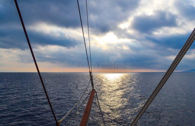 在风暴的帆船风帆 在黑暗的云彩前面 光从云彩的后面 库存照片