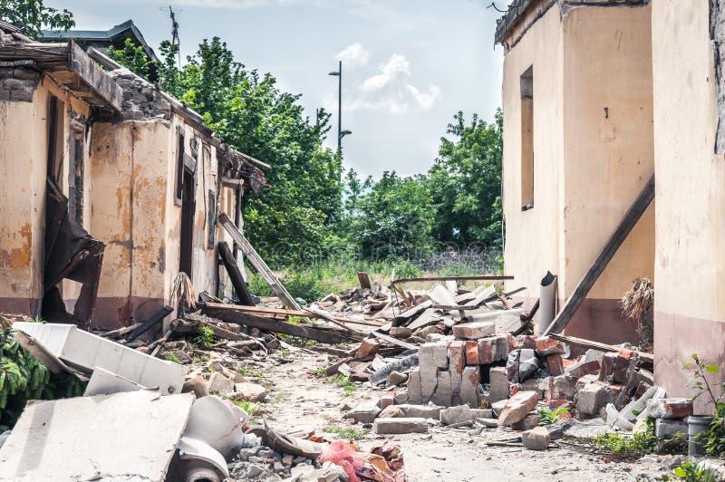 在飓风或战争灾害损坏的和被破坏的房子以后的后果浩劫崩溃了与喜怒无常和黑暗的天空的物产 免版税图库摄影