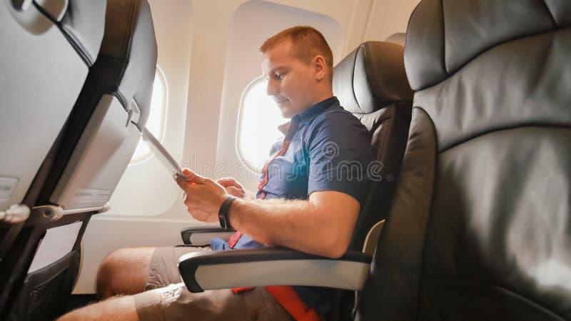在飞机上的一个年轻游人与片剂一起使用在离开前 库存图片