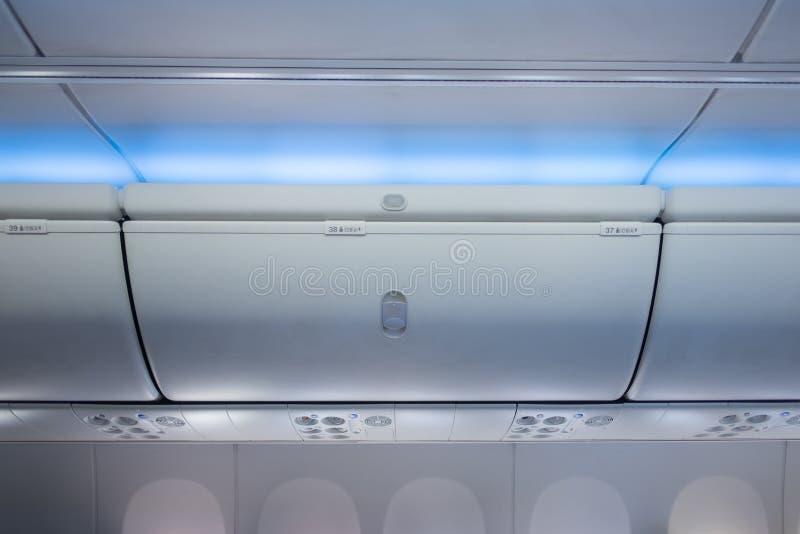 在飞机的顶上的衣物柜,内部在航空器 免版税库存照片