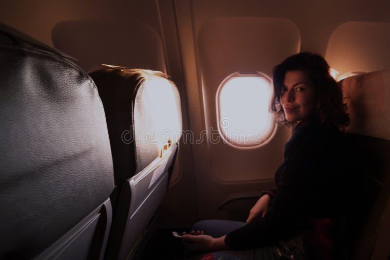 在飞机里面的年轻白种人妇女,微笑对照相机和 免版税库存照片