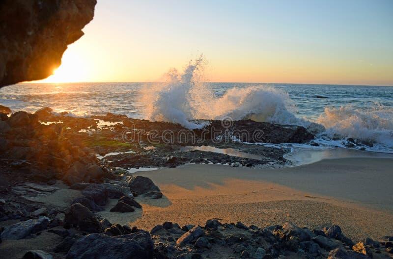 在飞溅波浪的日落在表在南拉古纳海滩,加利福尼亚的岩石海滩 免版税库存图片