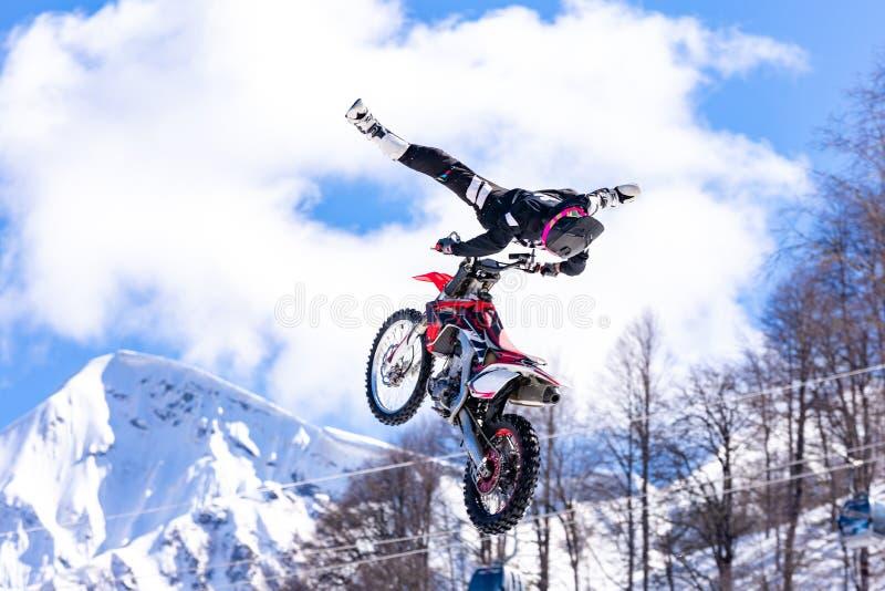 在飞行中摩托车的竟赛者,在跳板跳并且离开反对多雪的山 库存照片