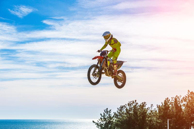 在飞行中摩托车的竟赛者,在跳板跳并且离开反对天空 图库摄影