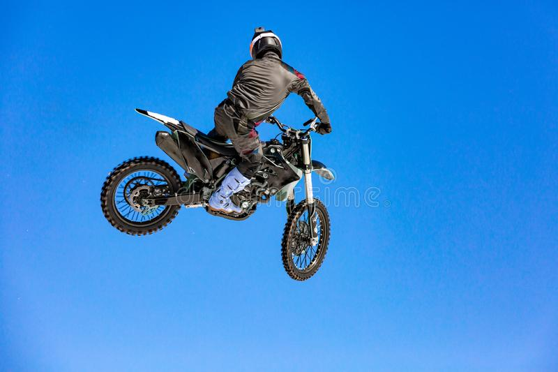 在飞行中摩托车的竟赛者,在跳板跳并且离开反对蓝天 库存照片