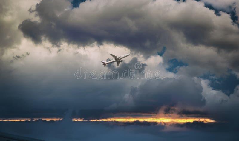 在飞行中白色客机 飞机飞行反对日落云彩 航空器侧视图 免版税库存照片