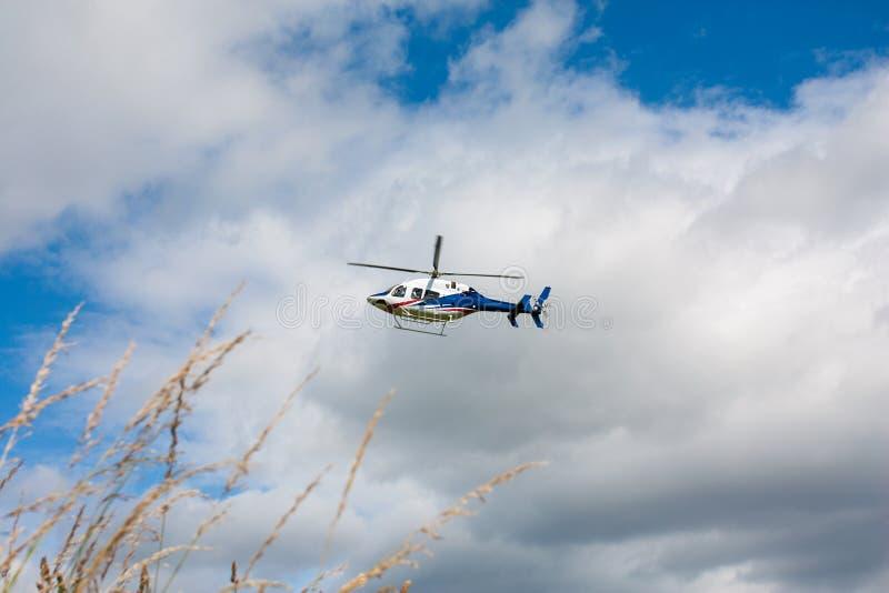 在飞行中白色蓝色红色被绘的直升机 免版税库存图片