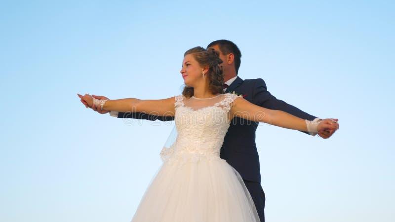 在飞行中跳舞和微笑对彼此的爱的男人和妇女 浪漫一起拥抱反对的夫妇人和女孩 库存图片