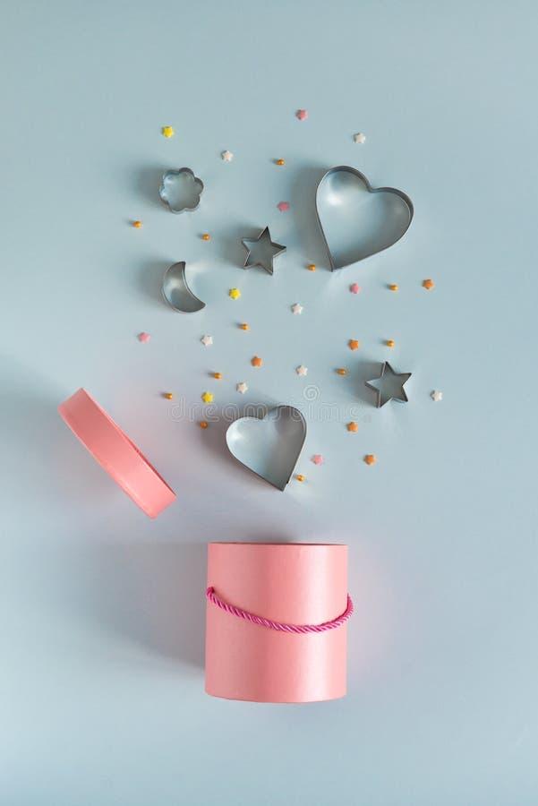 在飞行在蓝色背景的心形的金属曲奇饼切削刀桃红色礼物盒 奖金和销售概念 复制空间 免版税库存照片