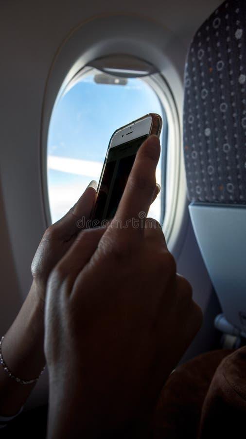 在飞行旅行期间的亚洲妇女藏品智能手机 在飞机上的旅行家 免版税图库摄影