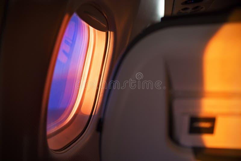 在飞行期间的窗口飞机 在橙色紫罗兰色口气的黎明 免版税库存照片